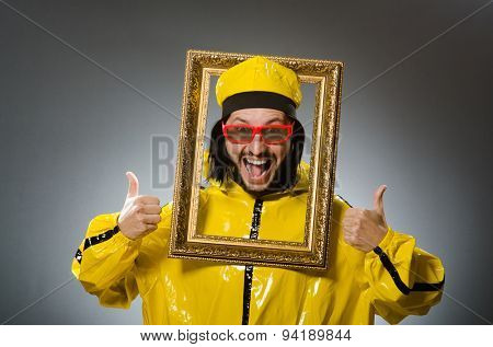 Man wearing yellow suit with picture frame