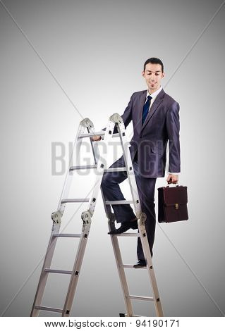 Businessman climbing career ladder against gradient