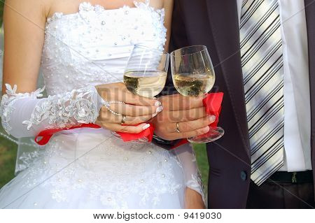 Glasses With Champagne In The Hands Of Groom And Fiancee