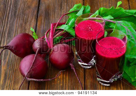 Glass of fresh beetroot juice with bets on wooden table