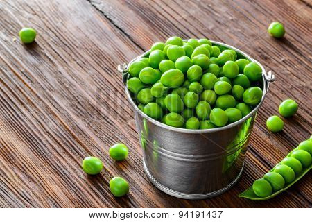 hearthy fresh green peas and pods on rustic wood table