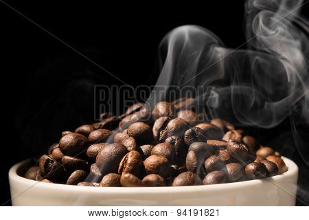Coffee mug full of coffee beans with smoke