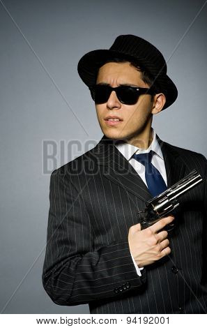 Young man in classic striped costume holding gun isolated on gray