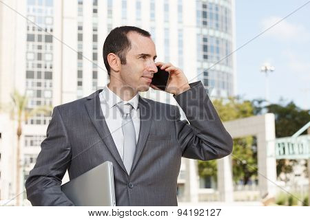 Handsome Young Businessman Using Mobile Phone In Front Of Modern Office Building