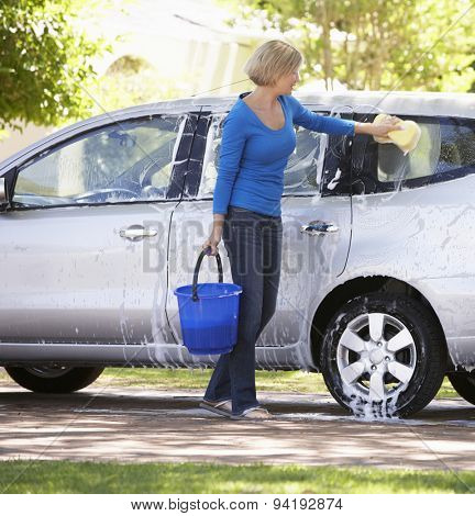 Woman Washing Car In Drive