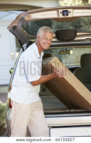 Senior Man Loading Large Package Into Back Of Car