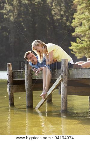 Romantic Couple Sitting On Wooden Jetty Looking Out Over Lake