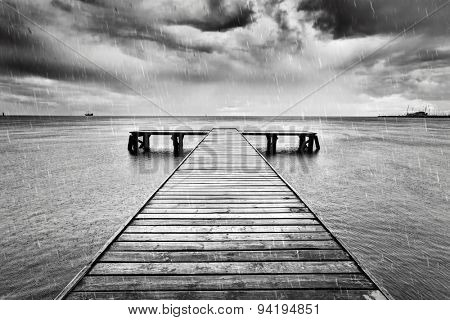 Old wooden jetty, pier on the sea. Raining from dramatic sky with dark, heavy clouds. Black and white