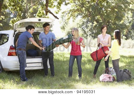 Group Of Young Friends Unloading Camping Equipment From Trunk Of Car