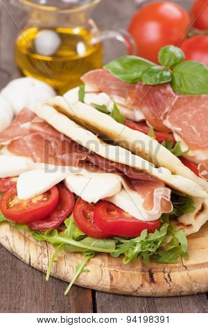 Piadina romagnola, italian flatbread sandwich with rocket salad, ricotta cheese and prosciutto