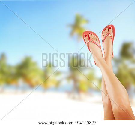Perfect female legs on sandy beach with sandals