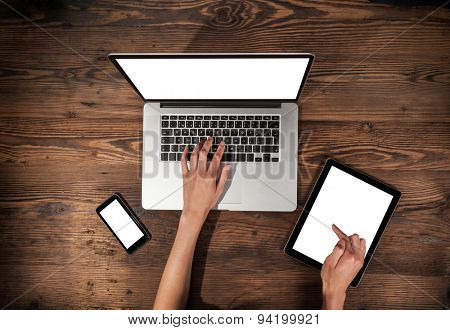 Aerial view of woman typing on laptop and tablet. Placed on wooden desk