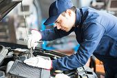 pic of auto garage  - Portrait of an auto mechanic at work on a car in his garage - JPG