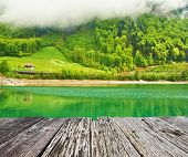 pic of dock a lake  - Beautiful emerald mountain lake in Switzerland under low clouds - JPG