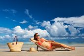 pic of woman bikini  - Woman in bikini lying on tropical beach at Seychelles - JPG