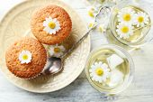 image of chamomile  - Glasses of chamomile tea with chamomile flowers and tasty muffins on color wooden background - JPG