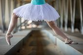 stock photo of tutu  - Cropped picture legs of graceful ballerina in white tutu in the industrial background of the bridge - JPG