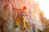 pic of climbing wall  - female rock climber climbs on a rocky wall - JPG