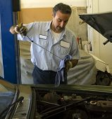 stock photo of car repair shop  - a mechanic checks the oil on a car being repaired - JPG