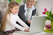 picture of granddaughter  - Smiling grandmother watching granddaughter using laptop - JPG