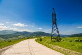 stock photo of power transmission lines  - High voltage electric power lines tower near the road in mountains - JPG