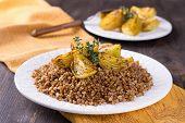 pic of buckwheat  - Buckwheat porridge with baked onions on a wooden table - JPG