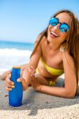 picture of suntanning  - Woman showing suntan cream bottle on the beach - JPG
