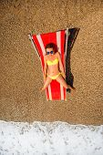 picture of sunbather  - Young and beautiful woman relaxing and having sunbath on the red sunbed in the sea - JPG