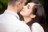 foto of cuddle  - Portrait of young beautiful brunette woman cuddling with her boyfriend kissing him in cheek with closed eyes and happy smile - JPG
