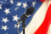 foto of united we stand  - Microphone on stand with US flag on background - JPG