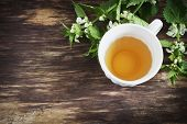 picture of nettle  - nettle tea and twigs of fresh nettle on the old wooden background - JPG