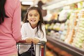 foto of trolley  - Close Up Of Mother Pushing Daughter In Supermarket Trolley - JPG