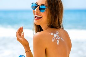foto of sunbathers  - Young woman with sun shape on the shoulder holding sun cream bottle on the beach - JPG