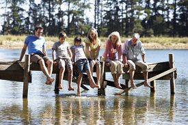 stock photo of jetties  - Three Generation Family Sitting On Wooden Jetty Looking Out Over Lake - JPG