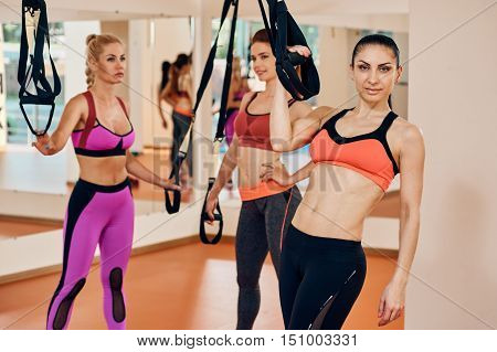 Women with trx fitness straps in the gym Concept workout healthy lifestyle sport. focus is on one girl