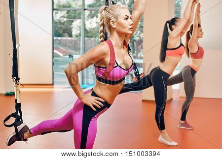 Group of women training at elastic rope in gym