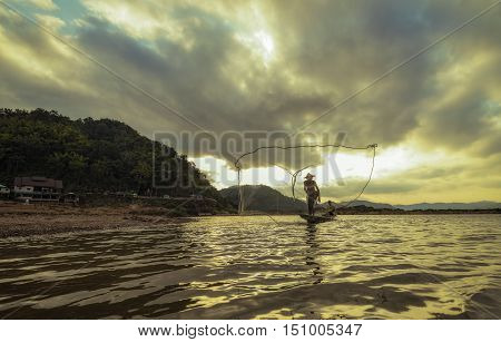 fisherman on wooden boat casting a net for catching freshwater fish
