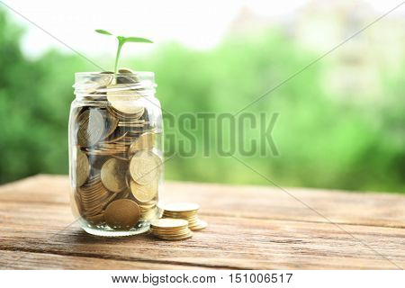 Jar with coins and green plant on wooden table, Financial investment concept