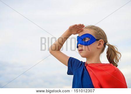 Superhero female kid looking into distance on sky background
