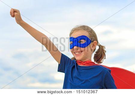 Smiling Superhero Kid Against Blue Sky Background.