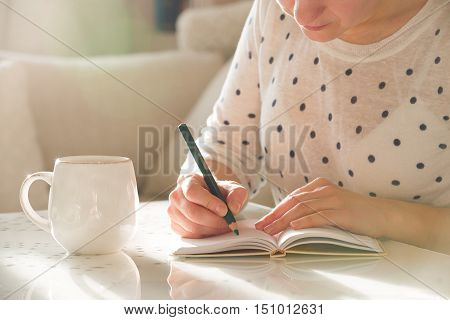 Woman sitting at the table writing in the notebook and drinking coffee in nice light home interior. Working at home. Freelancer. writing down ideas. indoors.