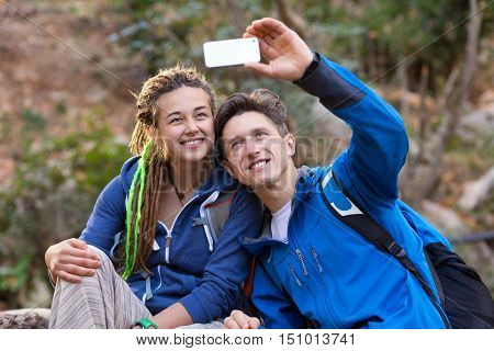 Young Family Handsome Man and Cute Woman with Hippie Hair Style taking self Portrait Photo with Camera of smart phone