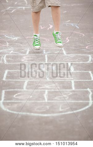 Closeup of boy's legs and hopscotch drawn on asphalt. Child playing hopscotch on playground outdoors on a sunny day. outdoor activities for children