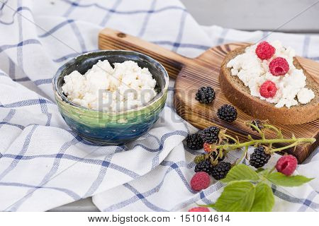 Organic Farming Cottage cheese in a green bowl slice of whole wheat bread with Homemade Ricotta cheese served with raspberries and blackberries on wooden board on linen fabric
