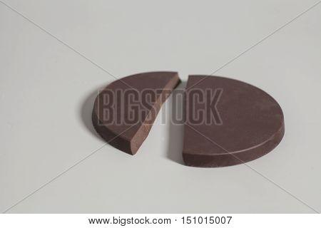 Broken round chocolate bar on a gray background
