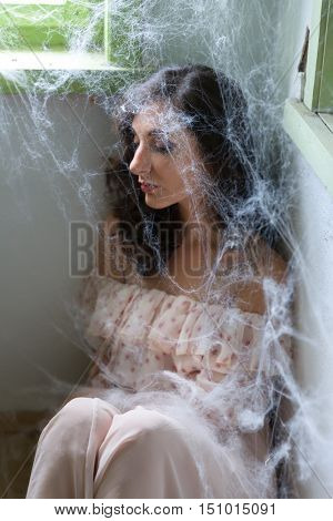 Young scared woman trapped in a corner with cobwebs or spiderwebs