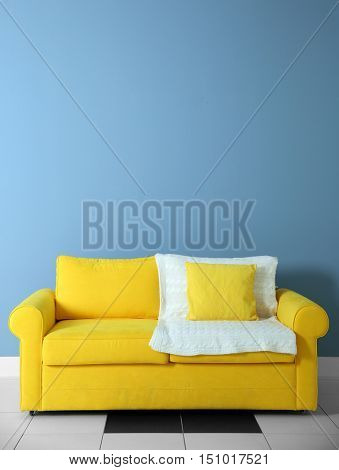Yellow sofa on blue wall background