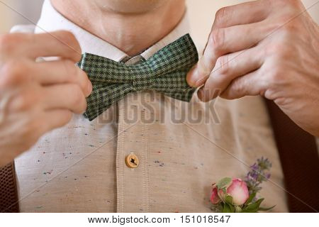 Stylish groom correcting bow tie