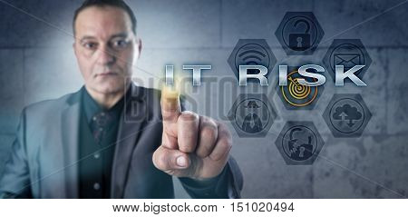 Determined corporate manager pressing IT RISK onscreen. IT concept and business metaphor involving computer security data security information technology management and security compliance.