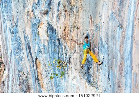Smiling male Rock Climber hanging on Rope at vertical unusual shape and colour natural rocky Wall  showing Okey hand sign